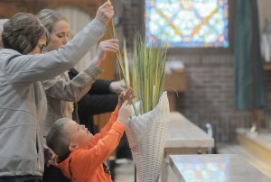 Denise Rieland, her daughter Lindsey Rieland and grandson Nolan Klaphake take palms during the Palm Sunday Mass at St. John Church in Meire Grove. Photo by Dianne Towalski / The Visitor