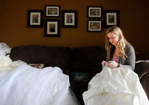 Sarah Zeroth does the delicate work of taking apart donated wedding dresses April 27 so the material can be reused to make garments for families grieving the loss of a child. (Dianne Towalski / The Visitor)
