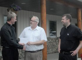 Deacon Randy Altstadt, center, and Father Matthew Kuhn, right, delivered cards and donations from the parishes of Holy Cross in Butler and St. Henry in Perham to Father Marvin Enneking, left, pastor of St. Mary Church in Melrose during a lunch meeting May 27. Photo by Dianne Towalski / The Visitor