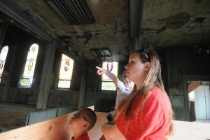"""Jill Van Beck brought her children to see the damage to St. Mary Church June 14. """"It's crazy to think that it could look like this,"""" she said. """"It's just so hard to believe."""" (Dianne Towalski / The Visitor)"""