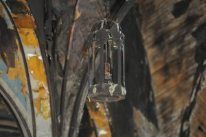 A burned light fixture hangs in the church. (Dianne Towalski / The Visitor)