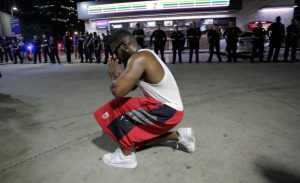 A protester prays near Dallas police officers July 7 after police officers were shot during a protest in Dallas. Snipers shot and killed five police officers and wounded seven more at the demonstration to protest the police killing of black men in Baton Rouge, Louisiana, and Falcon Heights, Minnesota. Two civilians also were injured in Dallas. (CNS photo/Ralph Lauer, EPA)