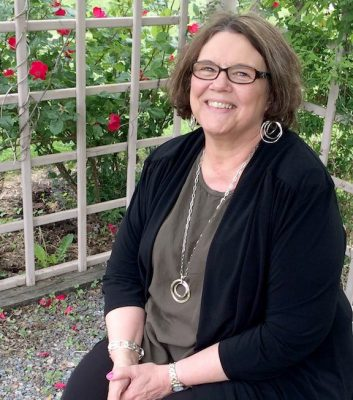 Angie Loecken, pictured here in the Pastoral Center garden, retires July 29 after more than 40 years with the Diocese of St. Cloud. (Photo by Wendy Gessell for The Visitor)