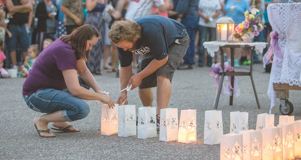 Mourners light the luminaries that were placed in a shape of a cross.  Photo by Paul Middlestaedt