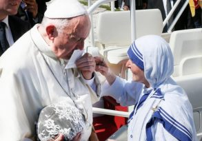 Pope Francis kisses a prayer card presented by a Missionaries of Charity nun at the conclusion of the canonization Mass of St. Teresa of Kolkata in St. Peter's Square at the Vatican Sept. 4. (CNS photo/Paul Haring)