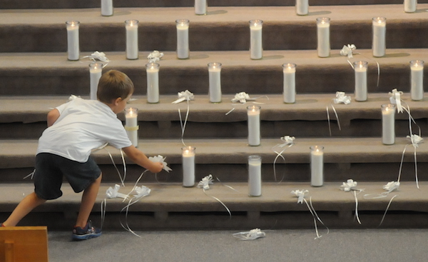 Anthony Scholz, 5, places one last white ribbon among the candles in the sanctuary during the service. (Dianne Towalski/The Visitor)