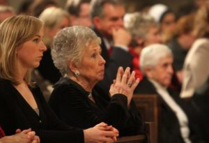 Joan Sheen Cunningham, niece of the late Archbishop Fulton J. Sheen, prays with her family during a 2009 memorial Mass for her uncle at St. Patrick's Cathedral in New York. The family of Archbishop Sheen has petitioned the Supreme Court of New York state to allow the transfer of the sainthood candidate's remains to Peoria. (CNS photo/Gregory A. Shemitz)