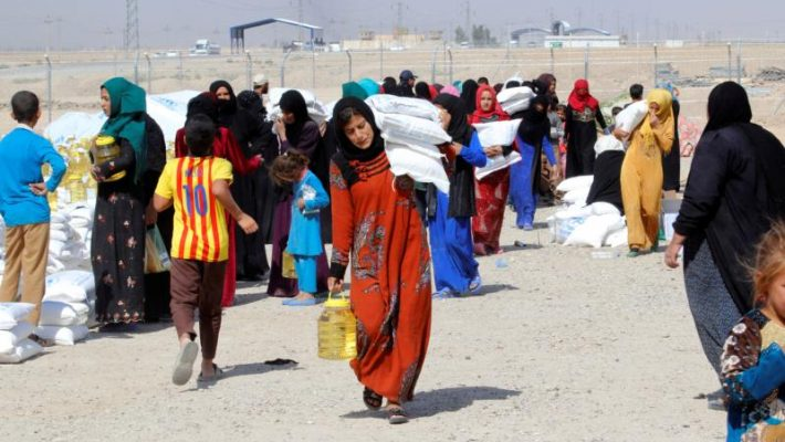 People who fled the Islamic State's strongholds of Hawija and Mosul receive aid Oct. 13 at a camp for displaced people in Daquq, Iraq. This summer, the U.N. said that as the Mosul crisis evolves, up to 13 million people throughout Iraq may need humanitarian aid by the year's end, far larger than the Syrian crisis. (CNS photo/Ako Rasheed, Reuters)