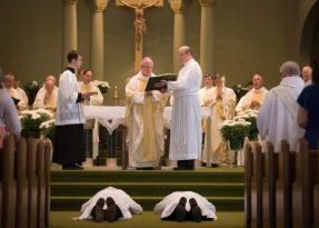 David Parker, left, and his son David Jr., lay prostrate during an ordination Mass at Assumption of the Blessed Virgin Mary Church in Pulaski, Wis., May 7. The elder Parker was ordained a permanent deacon and his son was ordained a transitional deacon as part of his formation for the priesthood. (CNS photo/Sam Lucero, The Compass)