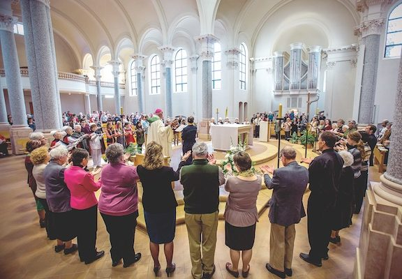 People involved in the health care profession surround Bishop Kettler for the Blessing of Hands at Sacred Heart Chapel. (Photo by Paul Middlestaedt)