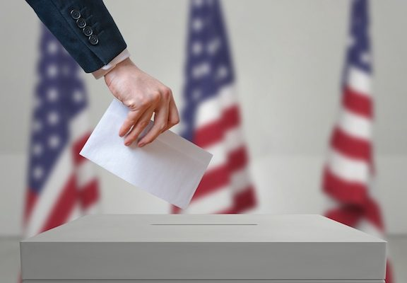 Election in United States of America. Voter holds envelope in hand above vote ballot. USA flags in background. Democracy concept.