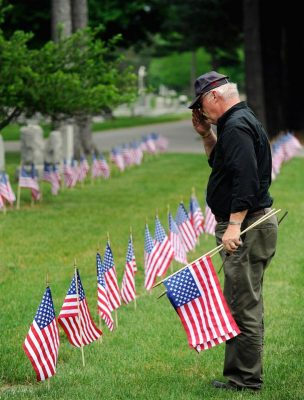 Vietnam veteran Tom Puff of American Legion Post 1830 in Chili, N.Y., salutes as he helps place American flags at military graves in 2013. (CNS photo/Mike Crupi, Catholic Courier)