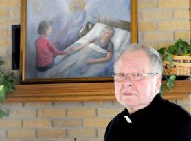 Father Silverius Schmitt stands near the painting he commissioned for Quiet Oaks Hospice House in St. Augusta. (Photo by Dianne Towalski/The Visitor)