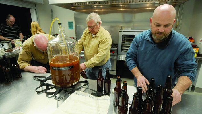 Mike Krause, center, fills sanitized bottles with beer from a glass carboy (vessel for fermenting beer or wine) with a siphoning tube with the help of Joe Whalen, left. Mark Hudson gets the filled bottles ready to be capped. Tim Kummet and Mariette Adelman take a break for some treats in the background.
